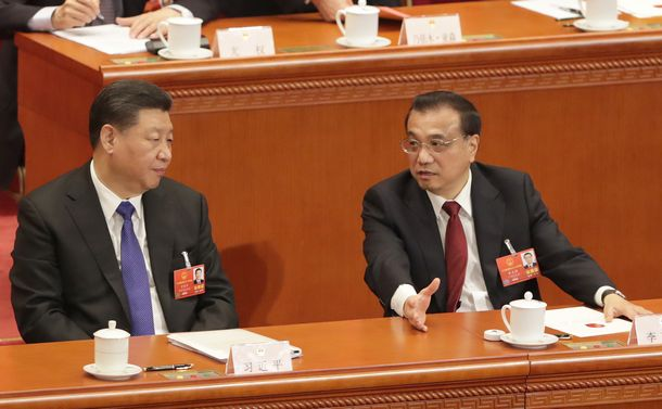 写真・図版 : 全人代で首相や国家監察委主任などを選出する投票が進む間、言葉を交わす李克強首相(右)と習近平国家主席=2018年3月18日、北京