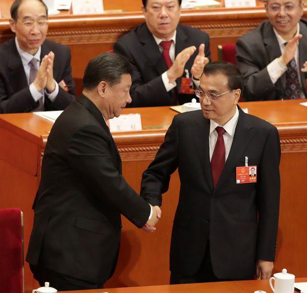 写真・図版 : 全人代で、首相に選出され握手する李克強首相(右)と習近平国家主席=2018年3月18日、北京