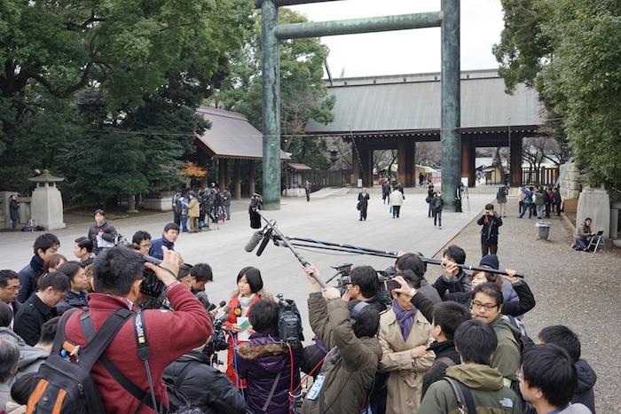 写真・図版 : 安倍首相の靖国神社参拝を中継後、日本メディアに取材される=2013年12月
