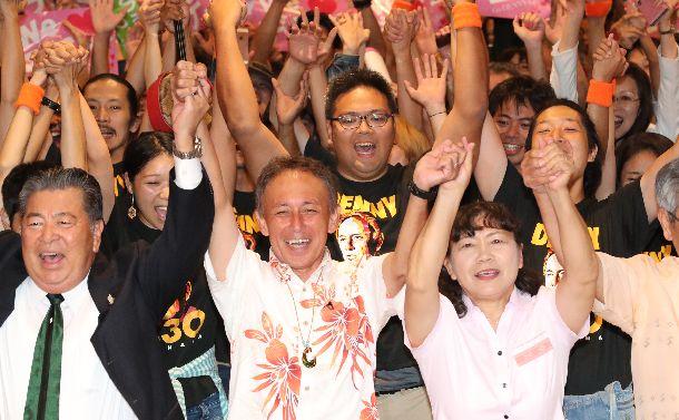 写真・図版 : 沖縄県知事選で自民党と公明党が推す候補を破り、当選を決めた玉城デニー氏(中央)=2018年9月30日