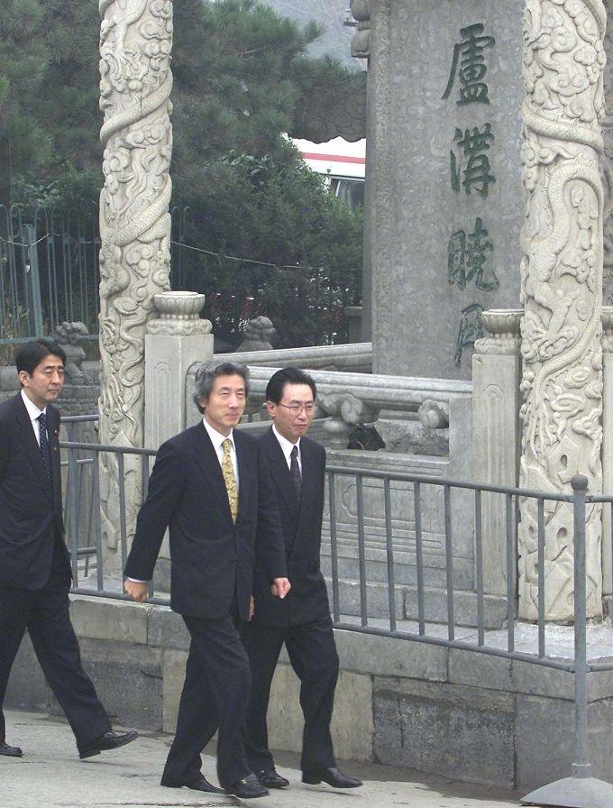 写真・図版 : 北京郊外の盧溝橋記念碑を視察する小泉純一郎首相。その後ろに当時官房副長官として同行した安倍氏がいる=2001年10月8日