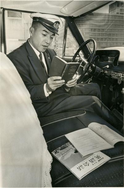 写真・図版 : 外国人客のために、客待ちの間も辞書を広げて英会話を勉強するタクシー運転手=1964年