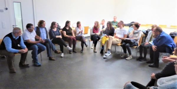 写真・図版 : 反省会で議論するドイツの学生と研究者たち