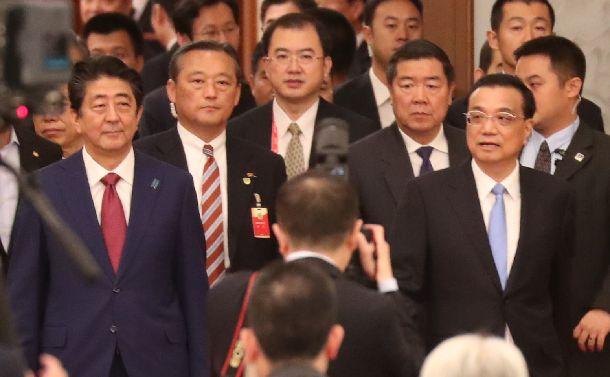 写真・図版 : 中国の李克強首相(右端)と共に第三国市場協力フォーラムの会場に入る安倍晋三首相(左端)=2018年10月26日、北京の人民大会堂