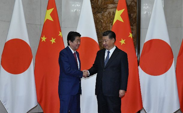 会談を前に握手する安倍晋三首相(左)と中国の習近平国家主席=2018年10月26日、北京の釣魚台国賓館