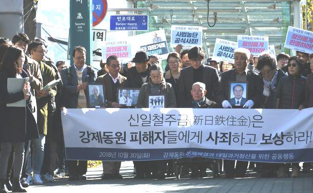 写真・図版 : 元徴用工の遺影を掲げ、韓国大法院に入る原告たち=2018年10月30日、ソウル
