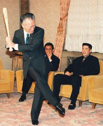 写真・図版 : 表敬訪問したイチロー選手(後方右)から贈られたサイン入りバットを振る村山富市首相=1994年12月12日、首相官邸