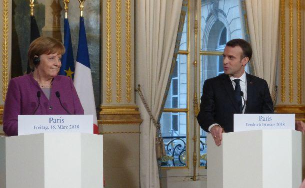 写真・図版 : 並んで会見するドイツのメルケル首相(左)とフランスのマクロン大統領=2018年3月16日、フランス大統領府