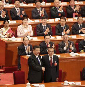 写真・図版 : 全人代で握手を交わす習近平国家主席(下段左)と李克強首相=2018年3月18日、北京