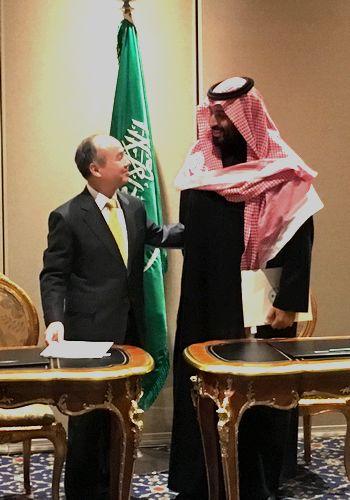 写真・図版 : サウジアラビアでの太陽光発電事業について覚書を交わした孫正義氏(左)とサウジのムハンマド皇太子=2018年3月27日、ニューヨーク