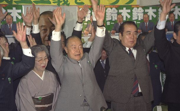 写真・図版 : 東京都知事選で4選を決めバンザイをして喜ぶ鈴木俊一氏(中央)。左は敦子夫人=1991年4月8日 、東京都新宿区