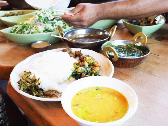 写真・図版 : 豆スープカレーとライスのほか、野菜炒めやキノコなどをふんだんに盛って頂いたダルバート
