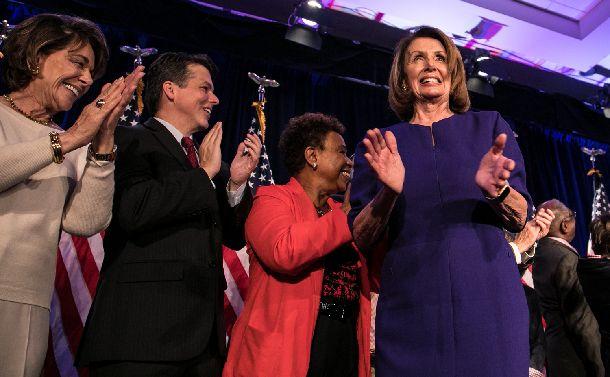 写真・図版 : 下院での民主党の勝利を受け、同僚議員らと喜ぶ同党下院のペロシ院内総務(右)=2018年11月7日、ワシントン