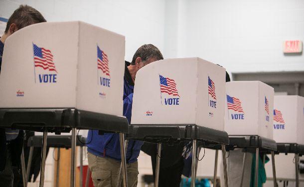 写真・図版 : 米中間選挙で投票用紙に記入する有権者ら=2018年11月6日、米メリーランド州シルバースプリング