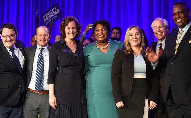 写真・図版 : ジョージア州知事選の候補ステイシー・エイブラムス氏(中央)ら民主党候補者。性別も人種も多様だ=2018年8月25日、同州アトランタ
