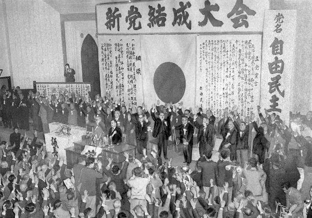 自由民主党の新党結成大会で万歳をする参加者たち= 1955年11月15日、東京・神田の中央大学講堂