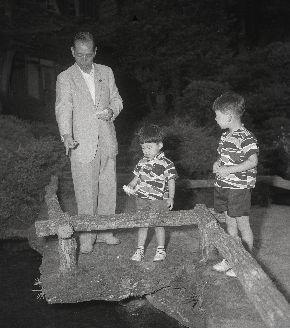 写真・図版 : 静養中、旅館の庭園で孫の安倍寛信(右)、晋三(左)両君とコイにえさをやる岸信介首相= 1957年7月7日、神奈川県箱根宮ノ下