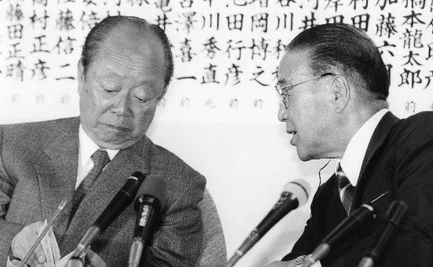 写真・図版 : テレビで衆院選の開票速報を見ながら話す宮沢喜一首相(左)と梶山静六自民党幹事長=1993年7月18日、自民党本部