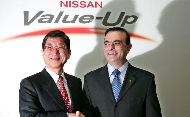 写真・図版 : 記者会見でゴーン氏と握手する志賀俊之氏=2005年2月21日、東京・銀座