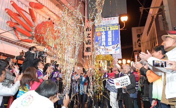 写真・図版 : 大阪万博の開催が決まり、道頓堀でくす玉を割って喜ぶ人たち=2018年11月24日、大阪市中央区