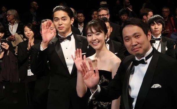 寝ても覚めても」の公式上映後、観客の声援に手をふる(右から)濱口竜介監督、唐田えりかさん、東出昌大さん