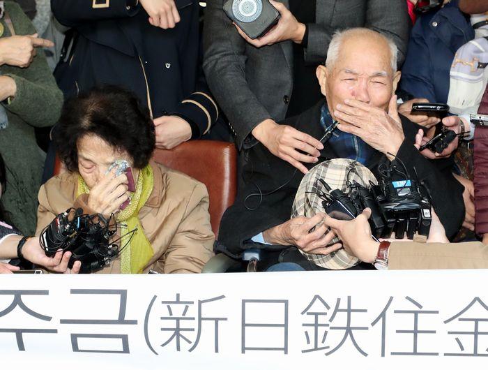 写真・図版 : 新日鉄住金に対する損害賠償訴訟で、10月30日の韓国大法院判決後に記者会見する元徴用工ら=東亜日報提供
