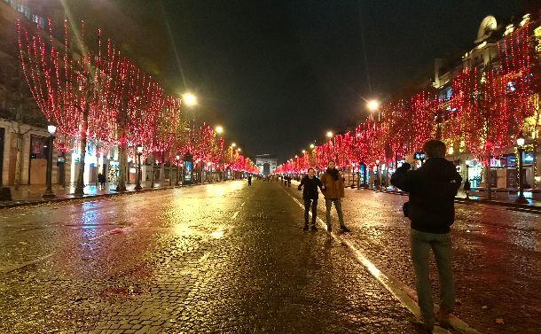 写真・図版 : デモが終わったシャンゼリゼ通り。赤色のイルミネーションで彩色された街路樹が輝く通りでは、歩行者が携帯で写真を撮っていた=2018年12月1日、パリ。筆者撮影