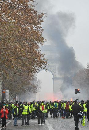 写真・図版 : パリの凱旋門近くでデモに参加する人たち=2018年12月1日、パリ
