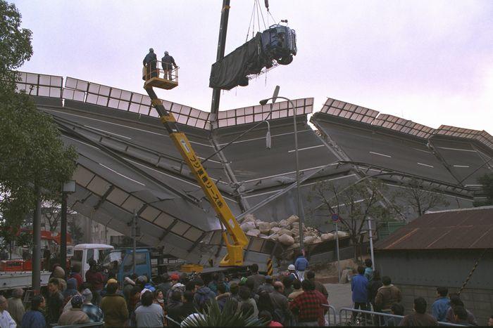 写真・図版 : 阪神・淡路大震災で倒壊した阪神高速道路神戸線からクレーンで運び出されるトラック=1995年1月18日