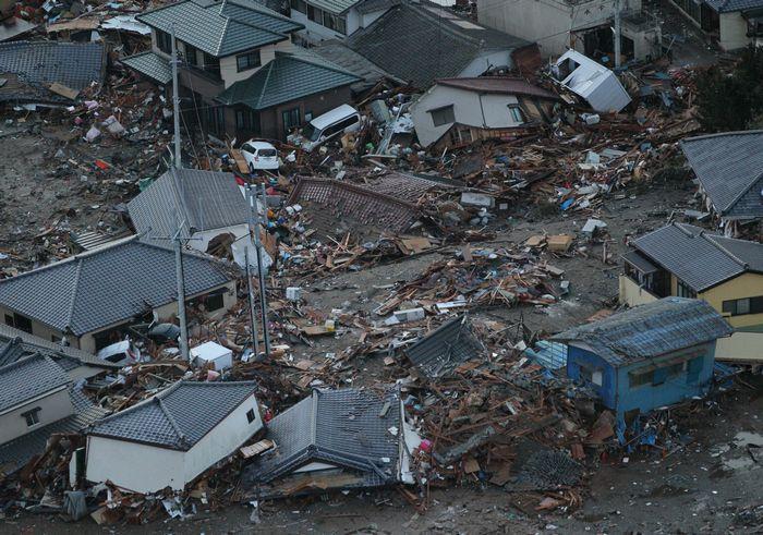 写真・図版 : 東日本大震災の津波によって、がれきの山となった住宅街=2011年3月11日、福島県いわき市