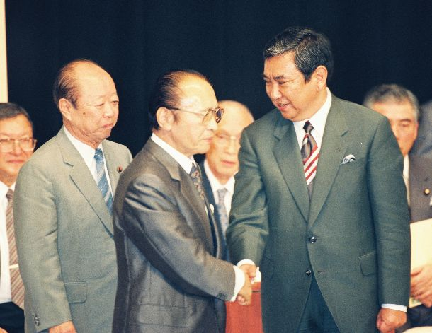 写真・図版 : 結党以来の野党に転落した自民党の新総裁に選出され、対立候補だった渡辺美智雄氏(左)と握手する河野洋平氏=1993年7月30日