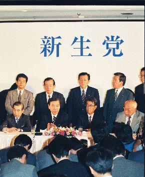 写真・図版 : 新生党結党の記者会見をする羽田孜党首(前列左から2人目)ら。壁には「新生党」の看板が掲げられている=1993年6月23日
