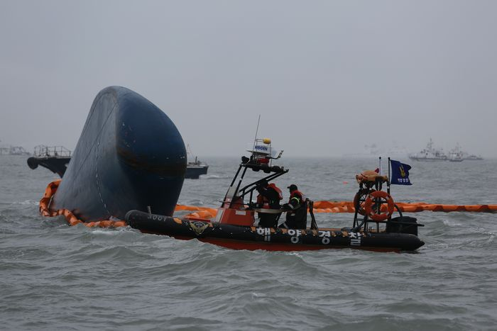 写真・図版 : 船首の一部を水上に出したまま沈没した旅客船セウォル号の周囲を捜索する韓国海洋警察庁のボート=2014年4月