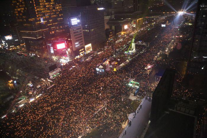 写真・図版 : 朴槿恵大統領(当時)の辞任を求める集会。参加者のろうそくで埋め尽くされた=2016年11月、韓国・ソウル市