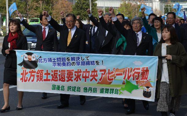 北方領土問題の早期解決を訴えて行進する元島民ら=2018年12月1日、東京都中央区