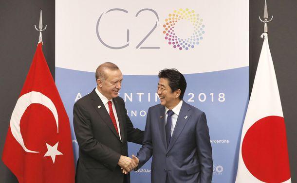 写真・図版 : 会談前にトルコのエルドアン大統領と握手する安倍晋三首相=2018年12月1日、ブエノスアイレス