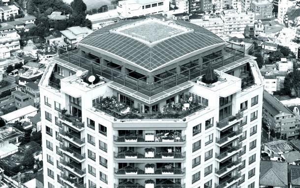 写真・図版 : 森ビルが開発した「元麻布ヒルズ」の「フォレストタワー」(地上29階、地下3階)。地上約103メートルのヘリポート部分は乾燥に強い多肉植物のセダム類で、周辺の傾斜面はネットに入れたスナゴケで覆っている。竹中工務店などが開発した屋上緑化システムだ=2002年、東京都港区元麻布