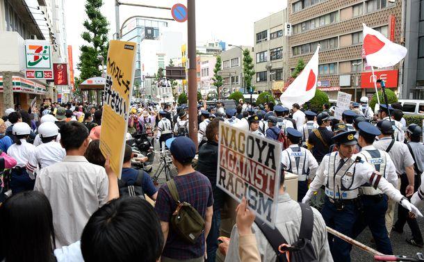 写真・図版 : 差別的な言葉を発しながら名古屋市中心部を行進するデモ隊(右側)。警備の警察官の列をはさんで反対派も声を上げながら横を歩いた=2016年5月29日、名古屋市中区