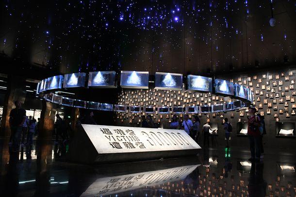 写真・図版 : 南京大虐殺記念館の本館へ入ると、暗い地下ホールの壁に犠牲者や生存者の顔写真が展示されている=2018年9月13日(冨名腰隆撮影)