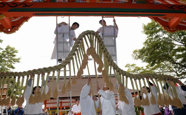 写真・図版 : 伏見稲荷大社本殿に長さ8メートルに注連縄を張る神職たち=2013年12月26日、京都市伏見区