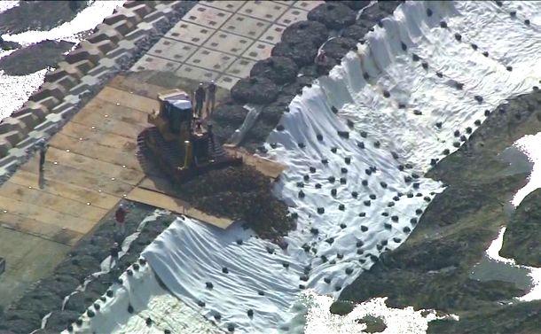 写真・図版 : 辺野古の海に土砂を入れる重機=2018年12月14日(琉球朝日放送提供)
