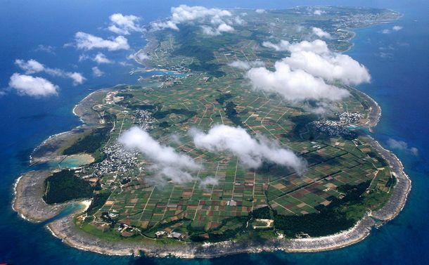 写真・図版 : 喜界島は鹿児島市から南へ380㎞、奄美大島の北東端から25㎞の洋上にある。周囲48.6㎞の小さな隆起サンゴ礁の島に、3,236世帯、6,839人が暮らしている(2018年11月1日現在、喜界町推計)=2007年7月6日、空撮