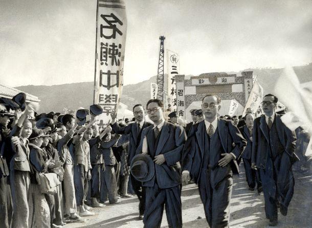 写真・図版 : 奄美群島は1953年12月25日に日本に返還された。復興のため政府調査団一行が奄美を訪れ、のぼり旗を立てて歓迎の人垣が出来た