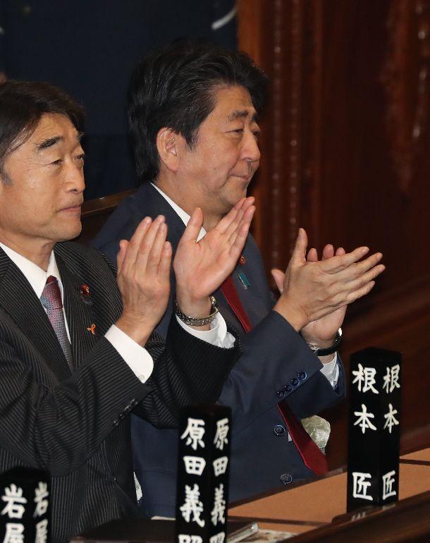 写真・図版 : 衆院本会議で入管法改正案が可決され、拍手する安倍晋三首相(右)=2018年11月27日