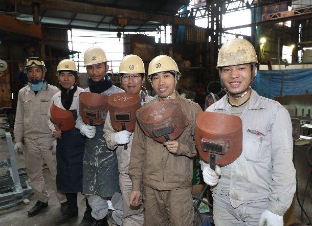写真・図版 : 溶接用の面を手にする外国人技能実習生ら=2018年10月11日、広島県尾道市の村上造船所