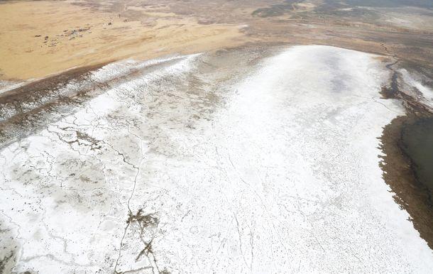 写真・図版 : 干上がり露出したアラル海の湖底を塩が覆う。左上がアケスペ村=2018年4月、カザフスタン