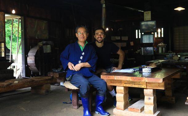 写真・図版 : 「妻籠を愛する会」の山内勉さんとイタリア人観光客=2018年8月29日、長野県南木曽町
