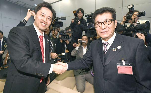 写真・図版 : 2025年の万博開催が決まり握手する松井一郎大阪府知事(右)と吉村洋文大阪市長=2018年11月23日、パリ