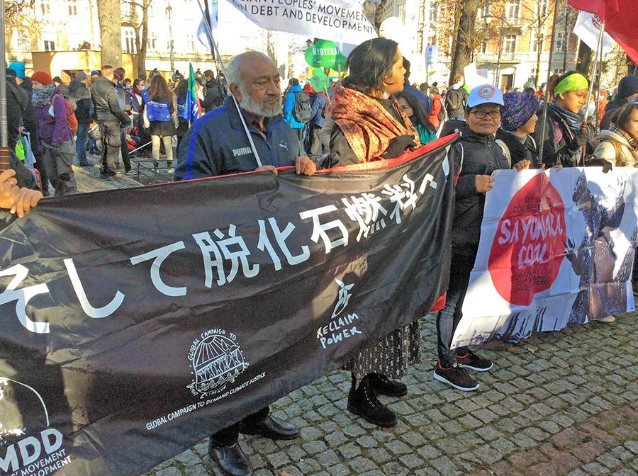 写真・図版 : COP24の会場周辺で訴える国際NGOのメンバーら=2018年12月8日、ポーランド南部カトビツェ、神田明美撮影