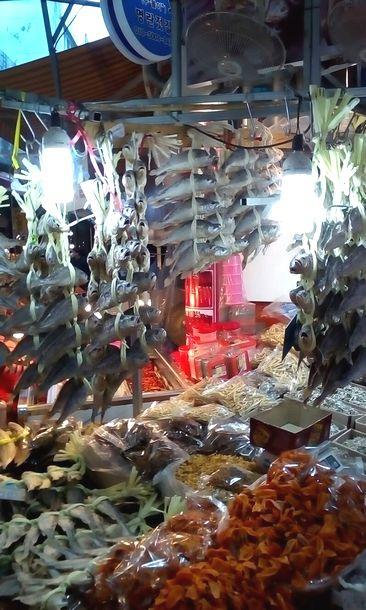 写真・図版 : ソウルの市場では、新年や旧正月の行事に備えてクルビ(奥に下がっているイシモチの干物)や干し柿(右手前)が山盛りになっていました